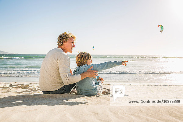 Father and son sitting on beach looking away pointing