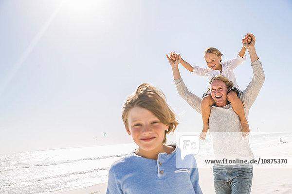 Vater und Söhne am Strand  mit lächelnden Schultern