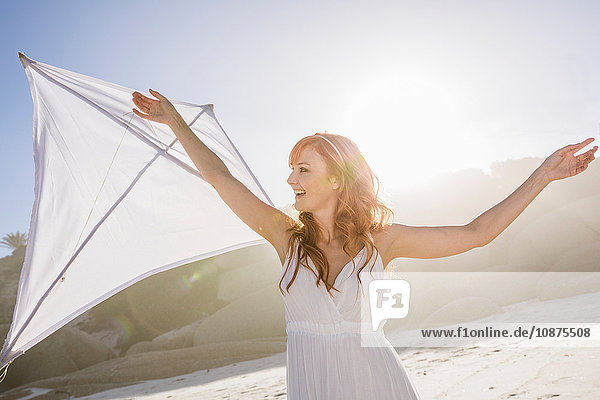Rothaarige Frau am Strand hält Drachen und schaut lächelnd weg