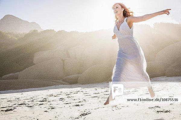 Frau in weißem Kleid mit offenen Armen am Strand hüpfend