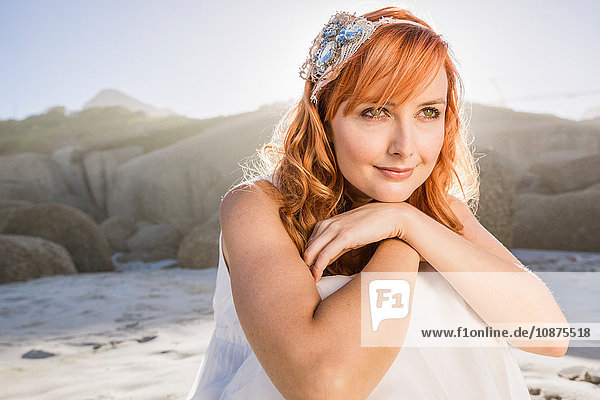 Porträt einer rothaarigen Frau  die am Strandkinn sitzend auf der Hand wegschaut