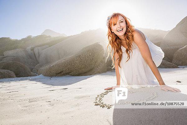 Frau kauert am Strand und zeichnet Herzform im Sand und schaut lächelnd weg