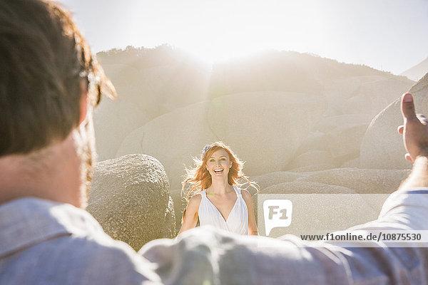 Lächelnder Blick über die Schulter des Mannes einer rothaarigen Frau