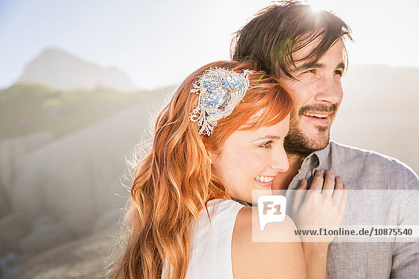 Man hugging red haired woman in front of rocks looking away smiling