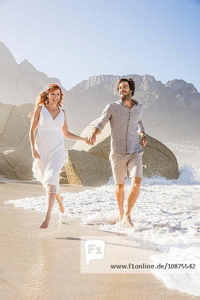Vorderansicht in voller Länge eines am Strand laufenden Paares  das sich an den Händen hält
