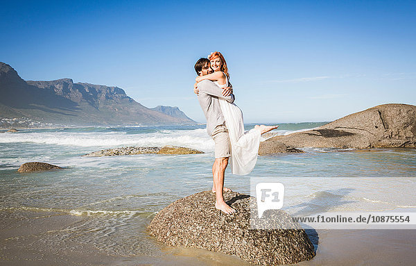 Seitenansicht in voller Länge eines Mannes  der auf einem Felsen steht und eine Frau hebt  die lächelnd in die Kamera schaut