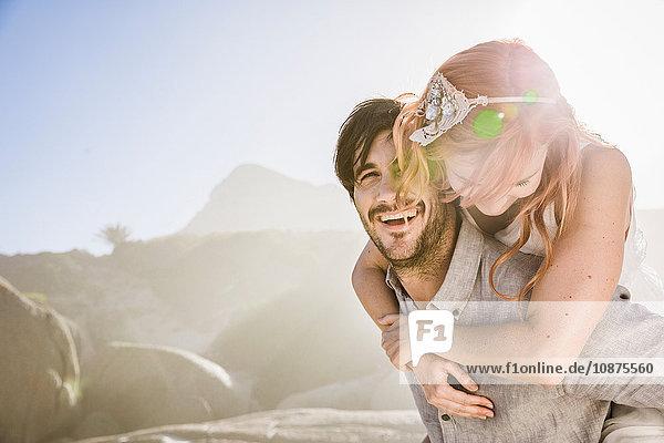 Mann vor Felsen gibt Frau huckepack lächelnd