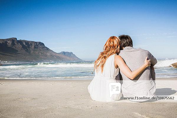Rückansicht einer Frau mit Arm um einen am Strand sitzenden Mann mit Blick auf den Strand