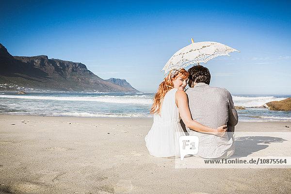 Rückansicht einer Frau mit Arm um einen Mann  der mit einem Regenschirm auf dem Strand sitzt und in die Kamera über die Schulter schaut