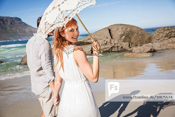 Paar hält sich an den Händen  geht an der Küste entlang  hält einen Regenschirm und schaut lächelnd über die Schulter in die Kamera