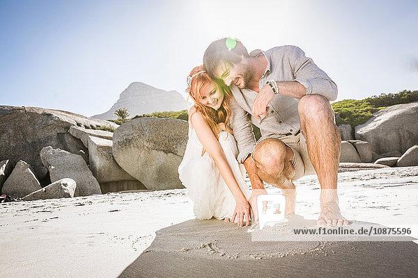 Am Strand kauerndes Paar zeichnet Herzform in Sand