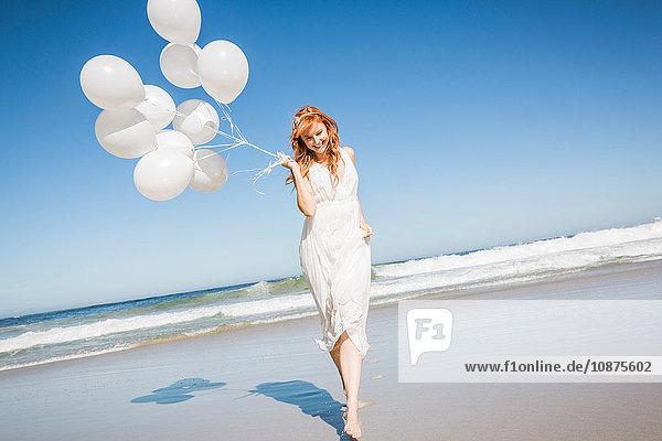 Frontansicht in voller Länge einer Frau am Strand  die ein weißes Kleid trägt und Luftballons hält