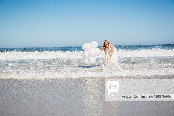 Frau knöcheltief im Ozean in weißem Kleid mit Ballons