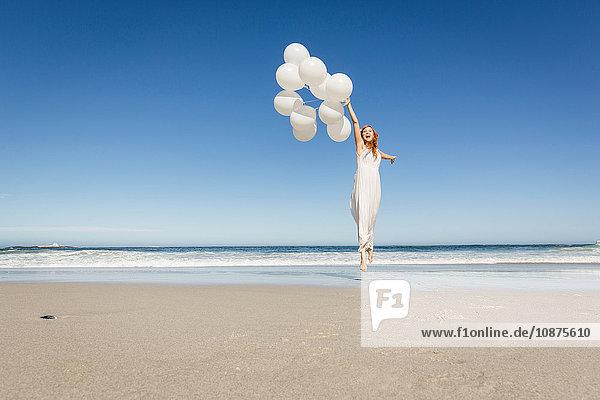 Vorderansicht einer Frau in voller Länge  die in weißem Kleid am Strand springt und Luftballons hält