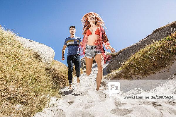 Paar im Freien  Händchen haltend  zum Strand hinunterrennend