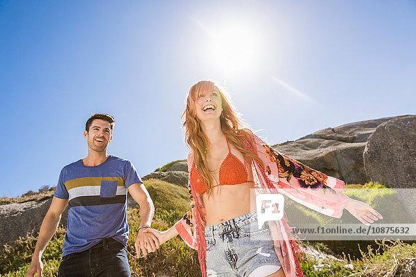 Paar im Freien  Händchen haltend  lachend