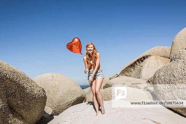 Junge Frau am Strand  die einen herzförmigen Ballon hält