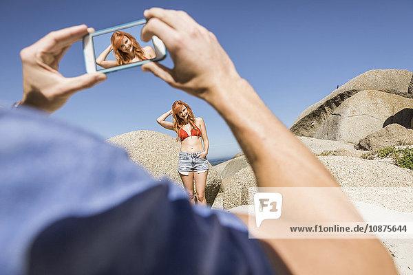 Mann fotografiert junge Frau  mit Smartphone  Rückansicht