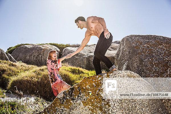 Paar im Freien  Mann hilft Frau beim Klettern