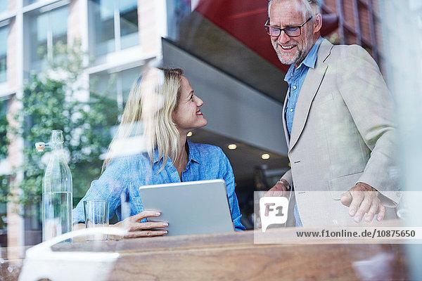 Reifer Mann und Frau im Café  die sich ein digitales Tablet ansehen