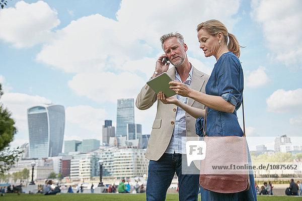 Erwachsener Mann und Frau im Freien  Blick auf digitales Tablet  Mann benutzt Smartphone