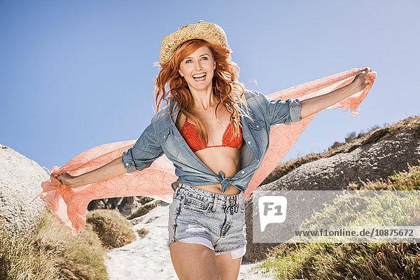 Porträt einer jungen Frau mit roten Haaren  im Freien  in Shorts und Bikinioberteil