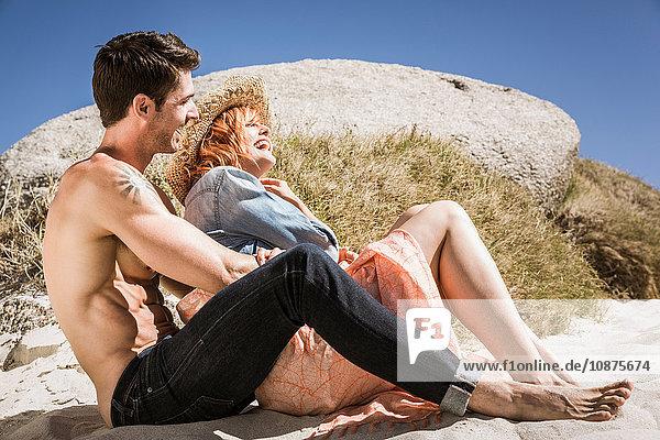 Paar am Strand sitzend  neben Felsen  lachend
