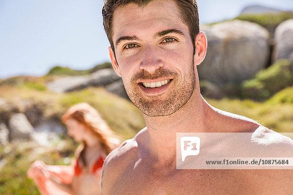 Porträt eines Mannes am Strand  lächelnd  junge Frau im Hintergrund