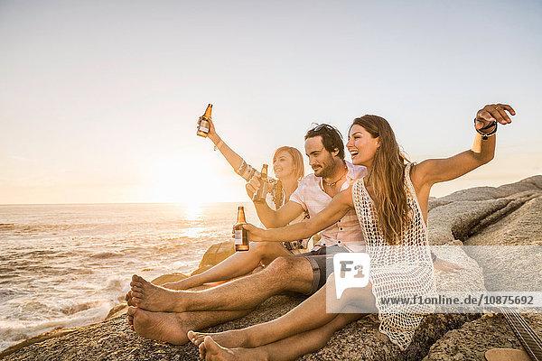 Drei mittelgroße erwachsene Freunde sitzen bei Sonnenuntergang am Strand und bringen einen Toast aus  Kapstadt  Südafrika