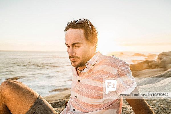 Mittlerer erwachsener Mann träumt am Strand bei Sonnenuntergang  Kapstadt  Südafrika