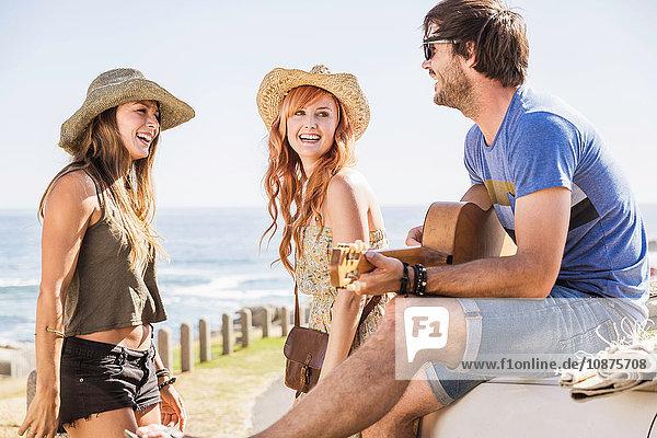 Mittlere erwachsene Freunde sitzen im Auto und spielen Gitarrenmusik an der Küste  Kapstadt  Südafrika