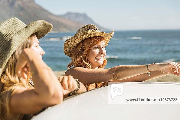 Zwei Freundinnen im mittleren Erwachsenenalter lehnen auf dem Autodach an der Küste  Kapstadt  Südafrika