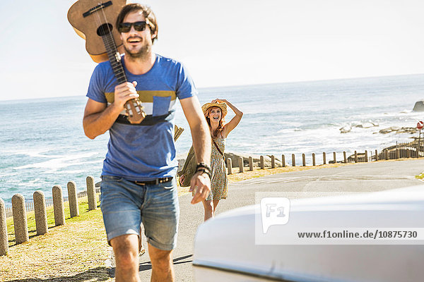 Mittelgroßes erwachsenes Paar mit Gitarre auf der Küstenstraße  Kapstadt  Südafrika