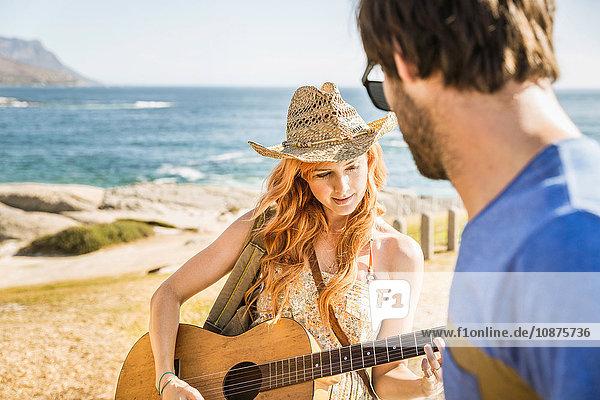 Mittleres erwachsenes Paar an der Küste  das Gitarre spielt  Kapstadt  Südafrika