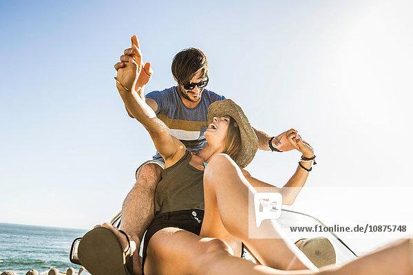 Mittelgroßes erwachsenes Paar  das auf der Küstenstraße Hände auf dem Autodach hält  Kapstadt  Südafrika