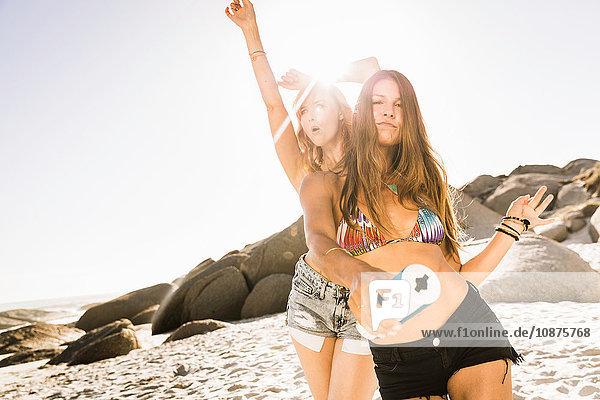 Mittlere erwachsene Freundinnen tanzen am sonnenbeschienenen Strand  Kapstadt  Südafrika