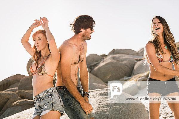 Drei erwachsene Freunde tanzen zusammen am Strand  Kapstadt  Südafrika