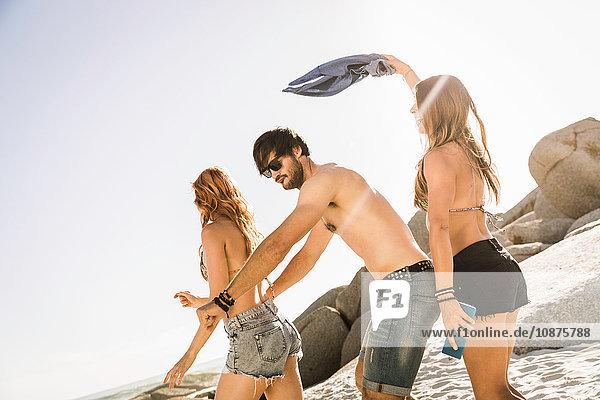 Drei erwachsene Freunde beim gemeinsamen Herumalbern am Strand  Kapstadt  Südafrika