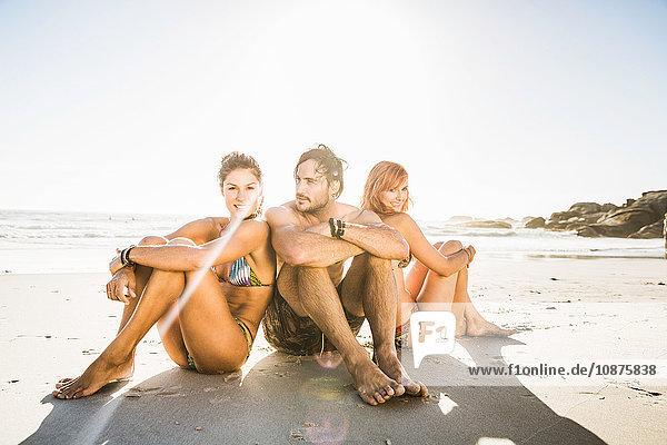 Drei mittelgroße erwachsene Freunde in Badebekleidung am Strand sitzend  Kapstadt  Südafrika