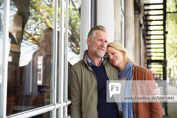 Reifes Paar lehnt lächelnd am Fenster