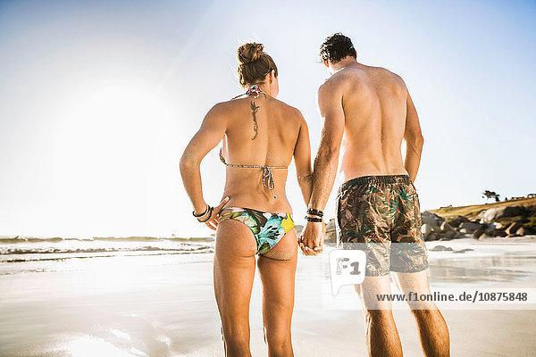 Rückansicht eines Pärchens im mittleren Erwachsenenalter in Shorts und Bikini am Strand  Kapstadt  Südafrika