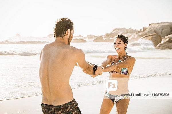 Paar mittlerer Erwachsener im Bikini und in Shorts  die sich am Strand drehen  Kapstadt  Südafrika