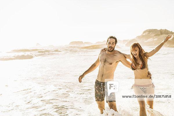 Mittelgroßes erwachsenes Paar rennt und planscht im Meer  Kapstadt  Südafrika