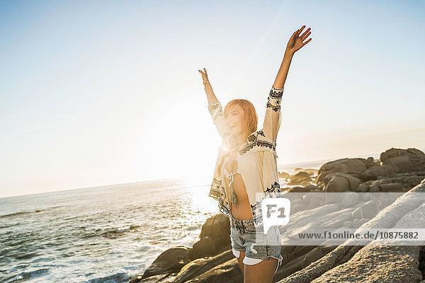 Mittlere erwachsene Frau am sonnenbeschienenen Strand mit erhobenen Armen  Kapstadt  Südafrika