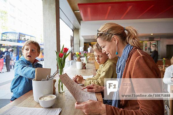 Mother and son at cafe looking at menu