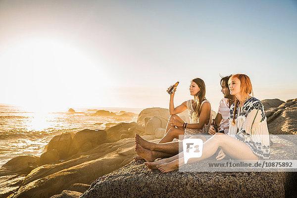 Drei mittlere Erwachsene sitzen am Strand und schauen auf den Sonnenuntergang,  Kapstadt,  Südafrika