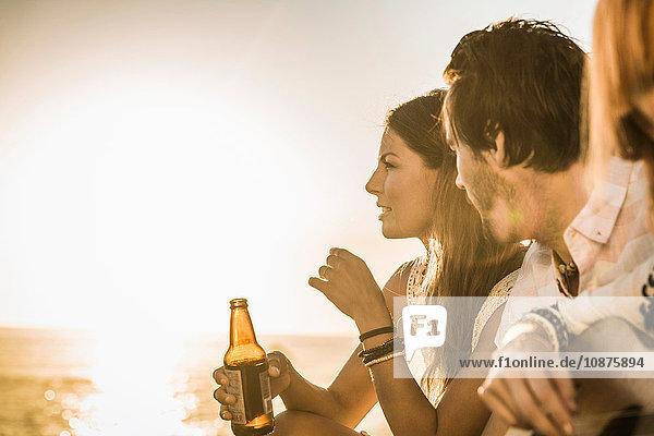Drei mittlere Erwachsene am Strand mit Blick auf den Sonnenuntergang  Kapstadt  Südafrika
