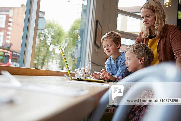 Mutter und Sohn am Fensterplatz im Café mit Laptop