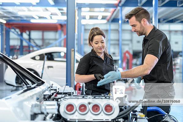 Ingenieure diskutieren über Auto in Rennwagenfabrik