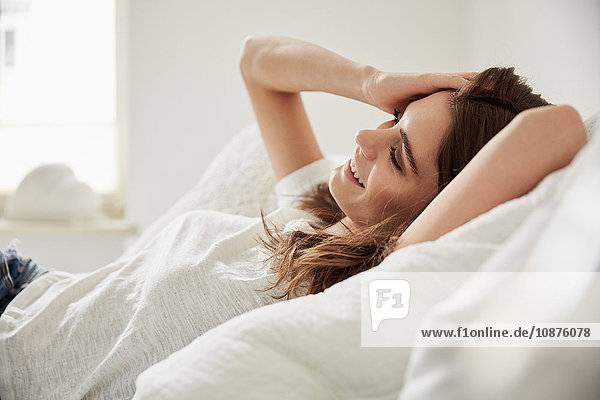 Oberflächenansicht einer schönen jungen Frau  die auf dem Bett liegt